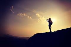 Fotógrafo da mulher que toma fotos no pico de montanha foto de stock