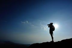 Fotógrafo da mulher que toma fotos no pico de montanha imagem de stock