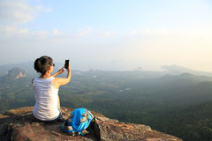 Fotógrafo da mulher que toma fotos no pico de montanha foto de stock royalty free