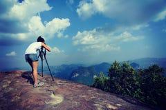 Fotógrafo da mulher que toma fotos no pico de montanha fotografia de stock
