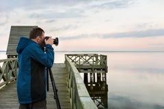 Fotógrafo da natureza que toma fotos do lago no por do sol Fotos de Stock
