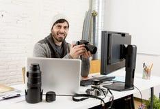 Fotógrafo de imprensa atrativo novo que guarda a câmera fotográfica que vê o seu trabalho na mesa de escritório do editor fotos de stock royalty free