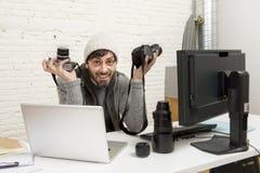 Fotógrafo de imprensa atrativo novo que guarda a câmera fotográfica que vê o seu trabalho na mesa de escritório do editor fotografia de stock