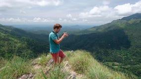 Fotógrafo de la aventura con los lanzamientos de la cámara mientras que se coloca en el mini pico de Adams en Sri Lanka Gran visi almacen de video
