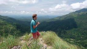 Fotógrafo de la aventura con los lanzamientos de la cámara mientras que se coloca en el mini pico de Adams en Sri Lanka Gran visi metrajes