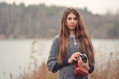 Fotógrafo de la muchacha con una cámara vieja en el lago foto de archivo