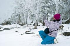 Fotógrafo de la muchacha en el fondo de un bosque de la montaña del invierno fotografía de archivo