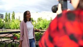 Fotógrafo de la muchacha, fotografiando a una mujer al aire libre, en el parque en un día nublado almacen de metraje de vídeo