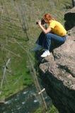 Fotógrafo de la mujer en el acantilado imagen de archivo libre de regalías