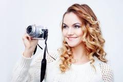 Fotógrafo de la mujer joven con la cámara, retrato en el fondo blanco Imagen de archivo libre de regalías