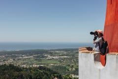 Fotógrafo de la mujer joven que toma la imagen del paisaje de la torre del castillo imagenes de archivo