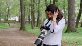 Fotógrafo de la mujer joven que trabaja tirar de proceso al aire libre en naturaleza del parque metrajes