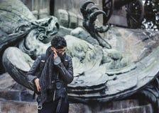 Fotógrafo de la mujer que comtempla por la estatua del águila del hierro fotografía de archivo