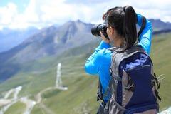 Fotógrafo de la mujer que toma la foto en el pico de montaña de la meseta en Tíbet, China Imagenes de archivo