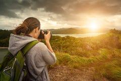 Fotógrafo de la mujer que viaja con la mochila que hace una inspiración Foto de archivo libre de regalías