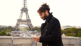 Fotógrafo de llamada modelo de sexo masculino brasileño cerca de la torre Eiffel en la cámara lenta