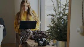 Fotógrafo de sexo femenino concentrado con la cámara y ordenador portátil que se sienta en alféizar en casa y que comparte sus fo imagen de archivo libre de regalías