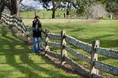 Fotógrafo de sexo femenino en el poste y la cerca de carril viejos Fotos de archivo