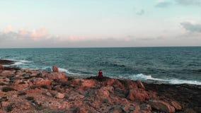 Fotógrafo de sexo femenino joven que busca un lugar para hacer las fotos en la costa rocosa hermosa con las olas oceánicas enorme metrajes