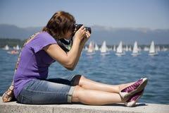 Fotógrafo de sexo femenino por el agua Imagenes de archivo