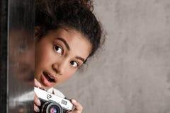 Fotógrafo de sexo femenino sorprendido que sostiene la cámara, mirando hacia fuera sobre fondo beige Fotos de archivo