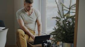 Fotógrafo de sexo masculino concentrado con la cámara y ordenador portátil que se sienta en alféizar en casa y que comparte sus f imagen de archivo libre de regalías