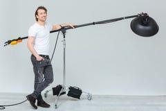 Fotógrafo de sexo masculino feliz que prepara el equipo de iluminación imagenes de archivo