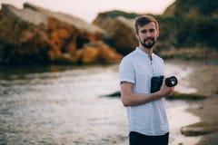 Fotógrafo de sexo masculino joven en la playa con la cámara digital Imagenes de archivo
