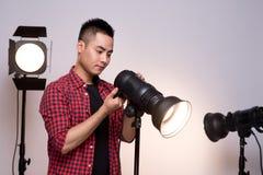 Fotógrafo de sexo masculino que prepara el equipo de iluminación en estudio fotos de archivo libres de regalías