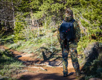 Fotógrafo del hombre del caminante en equipo del camuflaje con una mochila y un trípode que se colocan en un rastro del bosque de Imagen de archivo libre de regalías