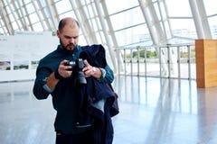 Fotógrafo del hombre joven que mira las imágenes de la sesión de foto pasada fotografía de archivo libre de regalías