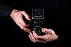 Fotógrafo del hombre que sostiene una cámara Proceso del tiroteo Cámara refleja de la foto de la cámara de la gemelo-lente media  imagen de archivo