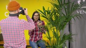 Fotógrafo del inconformista que toma la imagen del modelo de la raza mixta en café metrajes