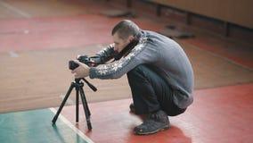 Fotógrafo del Neanderthal con la cámara en el trípode almacen de video
