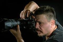 Fotógrafo del retrato con una cámara en fondo negro Fotografía de archivo libre de regalías