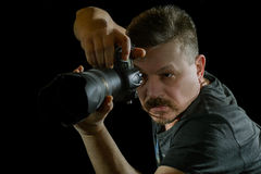 Fotógrafo del retrato con una cámara en fondo negro Imagen de archivo libre de regalías