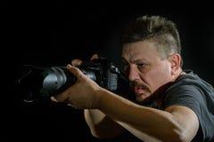 Fotógrafo del retrato con una cámara en fondo negro Imagenes de archivo