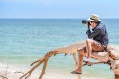 Fotógrafo do homem novo que toma fotos na praia Foto de Stock