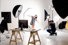 Fotógrafo e modelo bonito que trabalham no estúdio moderno da iluminação imagem de stock