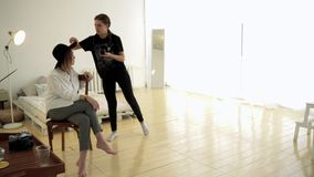 Fotógrafo e modelo da mulher antes de disparar media O fotógrafo corrige detalhes de modelo antes de tomar a imagem dentro vídeos de arquivo