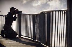 Fotógrafo en la silueta que toma las fotografías Fotos de archivo