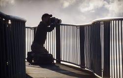 Fotógrafo en la silueta que toma las fotografías Foto de archivo libre de regalías