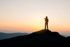 Fotógrafo encima de la montaña en el fondo de la puesta del sol Fotos de archivo
