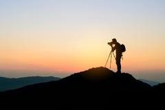 Fotógrafo encima de la montaña en el fondo de la puesta del sol Foto de archivo libre de regalías