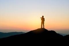 Fotógrafo encima de la montaña en el fondo de la puesta del sol Imagenes de archivo