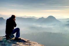 Fotógrafo exterior com tripé e câmera no pensamento da rocha Névoa grossa no campo outonal Trabalho do homem no clif afiado imagens de stock