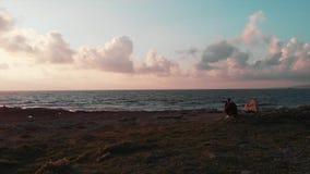 Fotógrafo fêmea atrativo novo que senta-se na praia rochosa e que toma fotos do por do sol bonito cor-de-rosa e do céu nebuloso m filme