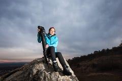 Fotógrafo fêmea com a câmera no tripé na rocha grande imagem de stock royalty free