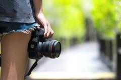 Fotógrafo fêmea que guarda a câmera do dslr Fotos de Stock
