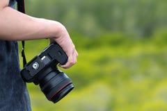 Fotógrafo fêmea que guarda a câmera do dslr Imagens de Stock Royalty Free